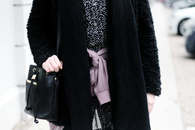 Outfit mit Pünktchenkleid und schwarzer Felljacke